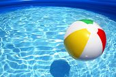 picture of beach-ball  - Colorful beach ball floating on a sparkling blue swimming pool - JPG