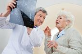 stock photo of radiogram  - Happy mature male doctor with senior female patient looking at x - JPG