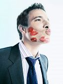 Businessman with lipstick marks over his face puckering over colored background