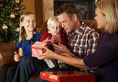 Familia apertura presenta delante de árbol de Navidad
