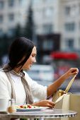 Image of happy female in open air cafe unwrapping ribbon of paperbag in urban environment