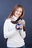 smiling woman in scarf with cup of tea