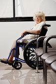 Постер, плакат: Портрет пожилой женщины на инвалидной коляске в вестибюле больницы
