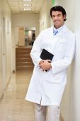 Portrait of a happy mixed race male doctor holding book while standing in hospital passageway