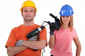 female and male tradespeople holding electric drill