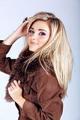smiling beautiful young woman with long blond hair wearing a suede fur coat on studio background