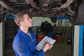 Male mechanic under car preparing checklist in workshop