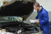 Male mechanic with clipboard examining car engine