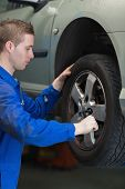 Male mechanic using lug wrench to change car tyre