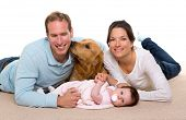 stock photo of puppies mother dog  - Baby mother and father happy family with golden retriever dog on carpet - JPG
