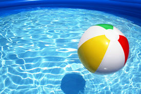 pic of beach-ball  - Colorful beach ball floating on a sparkling blue swimming pool - JPG