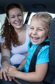 Happy Laughing Mother With Small Daughter In Car Safety Seat