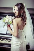 Young beautiful bride holding bouquet of flowers.