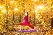 picture of virabhadrasana  - Yoga virabhadrasana warrior pose by beautiful woman in red cloth and yellow leaves around in the autumn - JPG