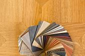 Different color samples of wood floor on brown parquet background.