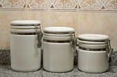 Three white ceramic jars on kitchen counter