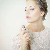 Girl with perfume, young beautiful woman holding bottle of perfume and smelling aroma, toned soft be