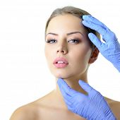 Beauty treatment of the young beautiful female face, doctor's hand in gloves touch face of beautiful