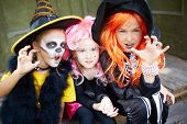 stock photo of warlock  - Portrait of three Halloween girls looking at camera with frightening gesture - JPG