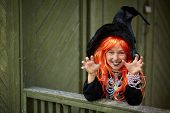 Portrait of Halloween girl with red hair wearing black hat