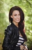 Beautiful young woman smiling wearing black leather jacket with long red hair