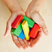 Two hands from above holding colorful building bricks
