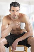 Interior portrait of a hot looking relaxed happy male model with a cup of morning coffee