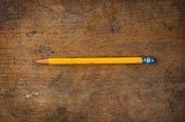 Old yellow pencil on a old used wooden desk.