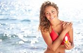 Young beautiful happy smiling cheerful tanned woman with sun-protection cream on beach, during sun b