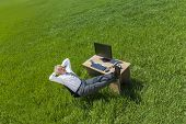 foto of field mouse  - Business aerial high angle concept shot showing an older male man or businessman relaxing feet up at a desk with a computer in a green field - JPG