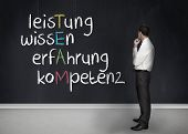 Elegant businessman looking at chalkboard with team anagram in german written on chalkboard