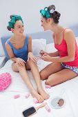 picture of slumber party  - Girls in hair rollers painting each others nails on bed at slumber party - JPG