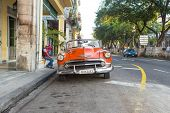 HAVANA, CUBA-SEPTEMBER 10:Vintage red Chevrolet parked near El Prado street September 10,2013 in Havana.These old classic cars have become an iconic sight and a tourist attraction in the Cuban cities
