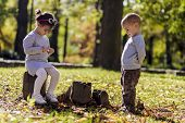 Litle Boy And Girl At The Autumn Forest