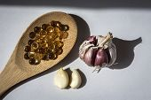 Pearls Of Garlic Oil On Wooden Spoon