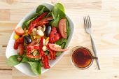 image of woodgrain  - Baby spinach salad with olives peppers and tomato served in a white bowl as a healthy lunchtime snack on a wooden table with a woodgrain pattern overhead view - JPG