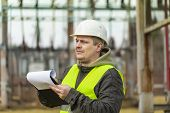 Electrical Engineer with folder in the electric substation