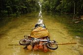 stock photo of raft  - Folding bycicle at raft flooded gravel road Papua New Guinea - JPG