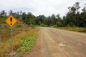 Yellow Warning Road Sign At Gravel Road