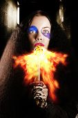 stock photo of fire-breathing  - Dark vertical photograph of a medieval jester performer breathing fire during a hot festival act at a middle ages carnival - JPG