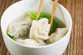 image of wanton  - Close up horizontal top view photo of freshly made wonton with chopsticks picking up single piece - JPG