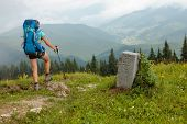 Hiker In Carpathian Mountains Near Frontier Stone