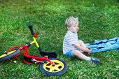 Little Boy Having Break On Green Grass After Riding Bicycle.