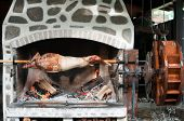 stock photo of water-mill  - Whole Roasted lamb on a barbecue driven by wooden water wheel - JPG