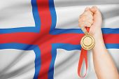 image of faro  - Sportsman holding gold medal with flag on background  - JPG