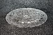 close-up horizontal view of new asphalt road and sewer manhole cover