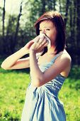 Young woman in summer dress standing on meadow during sunny day  and wiping her nose. Girl with runny nose, having allergy and holding a tissue next to her face.