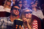stock photo of popcorn  - Happy couple sitting in movie theater - JPG