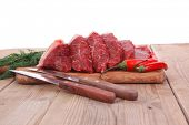 fresh raw beef meat steak's on wooden cut board over wooden table with dill and stainless steel knif