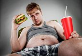 foto of big-foot  - Fat man eating hamburger seated on armchair - JPG